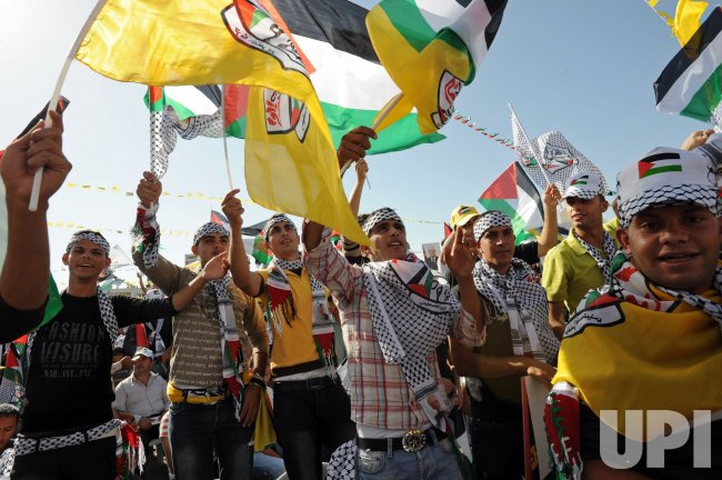 Palestinians wave the Palestinian and Fatah flags at a rally to support Fatah and commemorate the sixth anniversary of Yasser Arafat's death