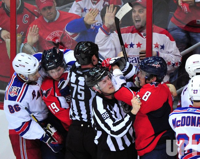 Linesman David Brisebois holds back Capitals' Alex Ovechkin in Washington