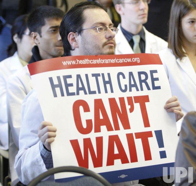Garces holds a sign during Sen. Burris' speech in Chicago