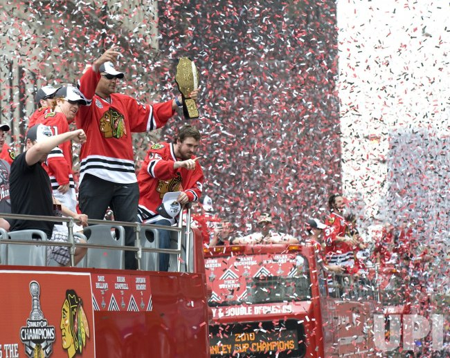 Chicago Blackhawks Brian Campbell, Dustin Byfuglien and Dave Bolland wave to fans during victory parade