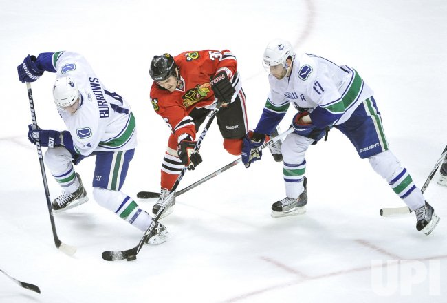 Blackhawks Bolland knocks puck away from Canucks Burrows and Kesler in Chicago