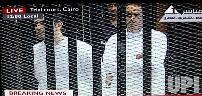 Video image of Alaa Mubarak and Gamal Mubarak, sons of Hosni Mubarak, in a cage during trial in a Cairo courtroom
