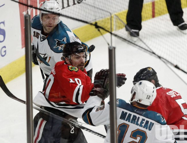 Blackhawks Sharp and Sharks Marleau go for the puck in Chicago