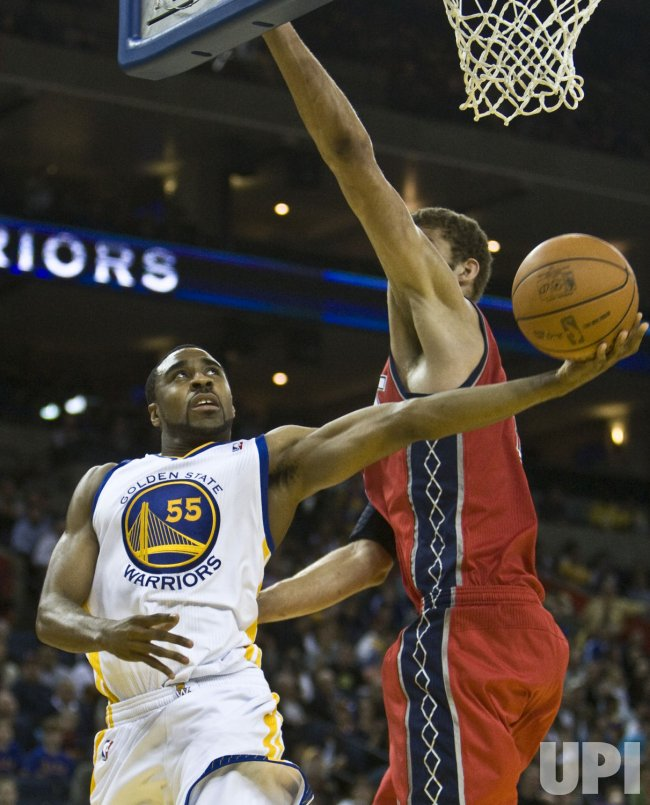 Warriors Reggie Williams reverses a shot around New Jersey Nets Brook Lopez in Oakland, California