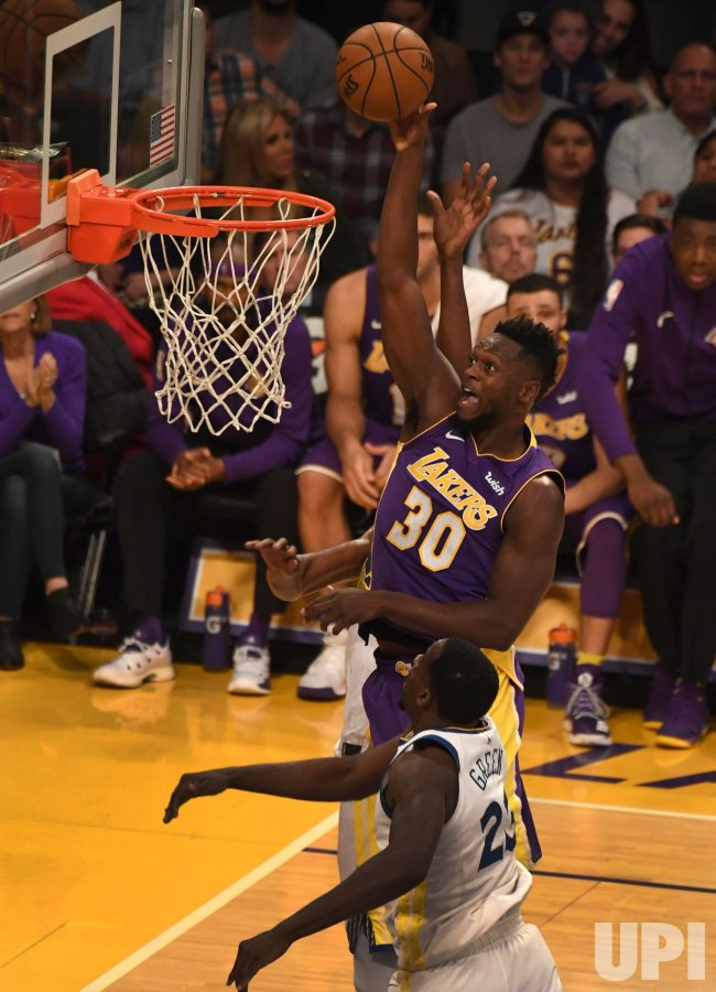 Lakers forward Julius Randle shores over Warriors Draymond Green in Los Angeles
