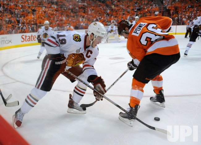 Blackhawks Jonathan Toews and Flyers Darroll Powe fight for the puck during the 2010 Stanley Cup Final