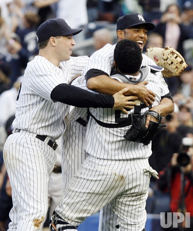 New York Yankees Mariano Rivera is hugged by Mark Teixeira and Jose Molina after the Yankees defeated the the Boston Red Sox 4-2 and win the American League East at Yankee Stadium in New York