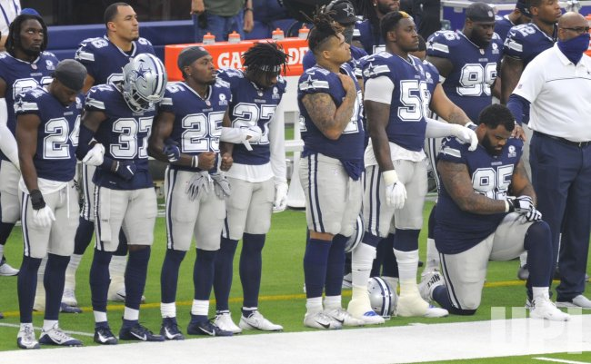 Cowboys listen to the National Anthem before the game against the Rams