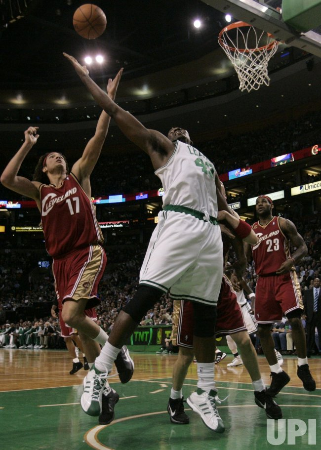 Celtics Perkins and Cavaliers Varejao reach for rebound in Boston, MA.