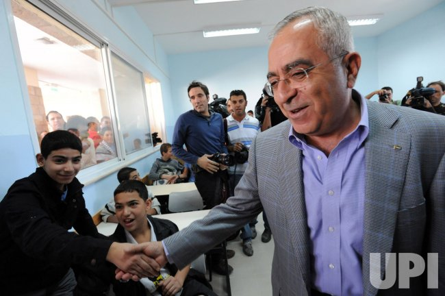 Palestinian Prime Minister Salam Fayyad shakeshands with a student at the inauguration of a new school wing in East Jerusalem
