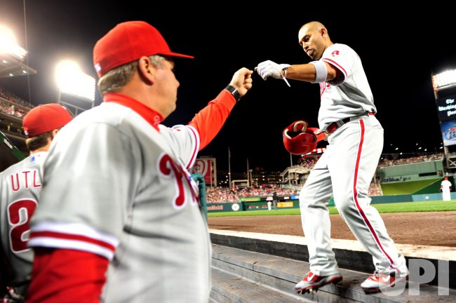 Phillies' Shane Victorino is congratulated after scoring in Washington