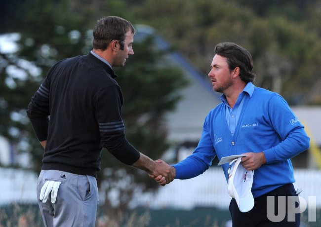 Dustin Johnson shakes hands with Graeme McDowell during the U.S. Open in Pebble Beach, California