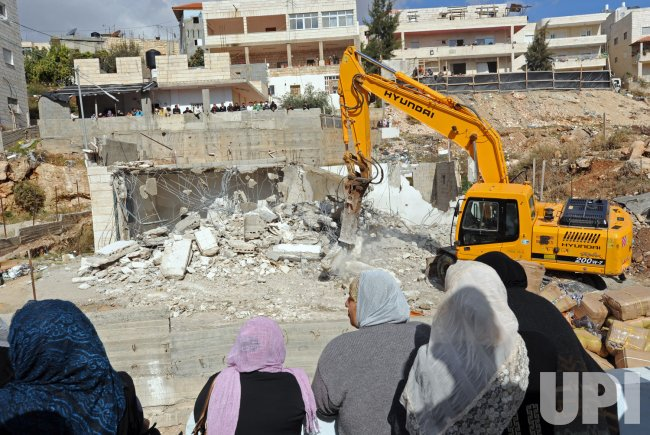 Palestinians watch the demolition of a building in east Jerusalem
