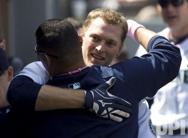 Seattle Mariners' Michael Saunders is hugged by Felix Hernandez after hitting a solo home run against the Los Angeles Angels.