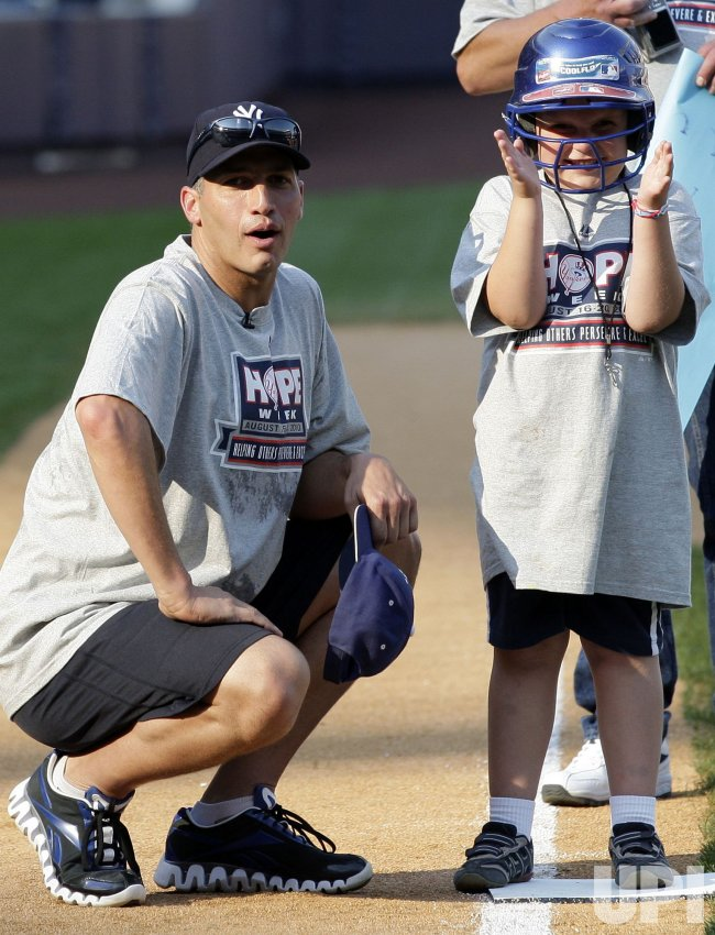 A child from Beautiful People and New York Yankees Andy Pettitte at Yankee Stadium in New York