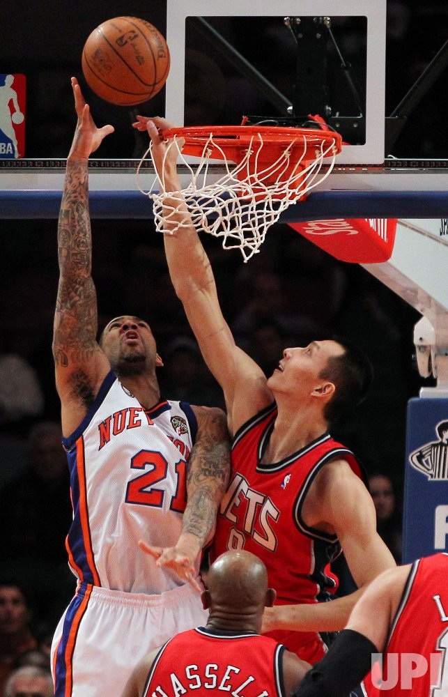 New Jersey Nets Yi Jianlian sticks his hand through the basket while playing defense on New York Knicks Wilson Chandler at Madison Square Garden