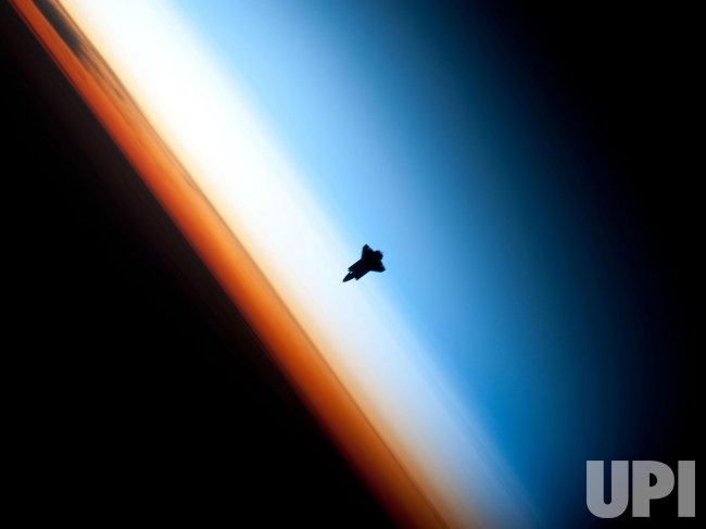 Endeavour Space Shuttle STS-130 Mission silhouetted by Earth.