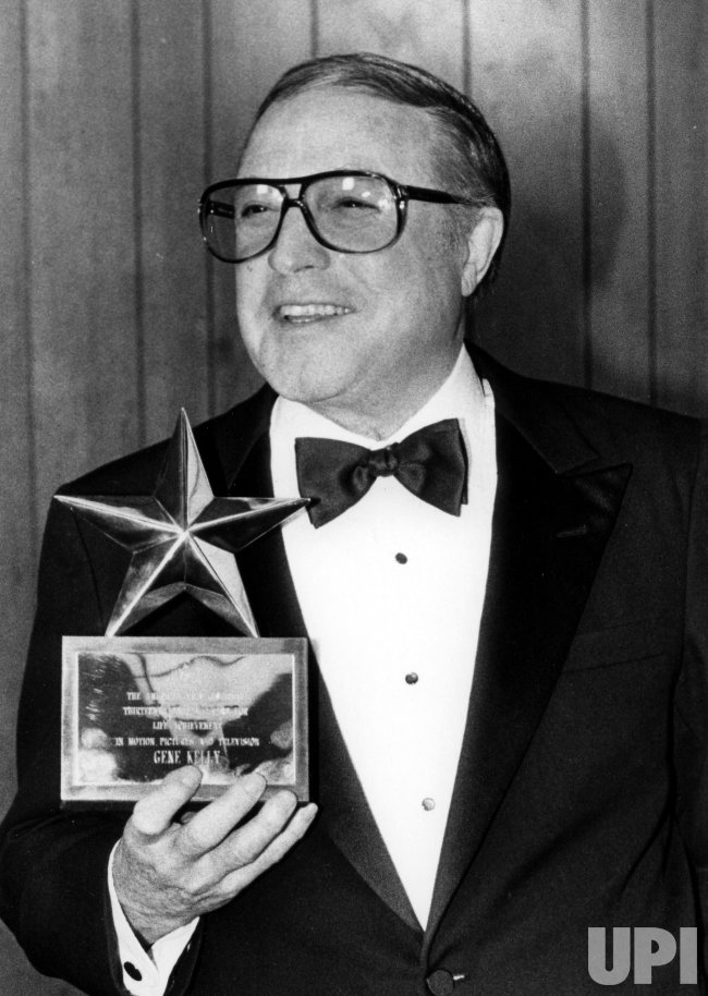 A beaming Gene Kelly holds his American Film Institute Life Achievement award at a photo session.