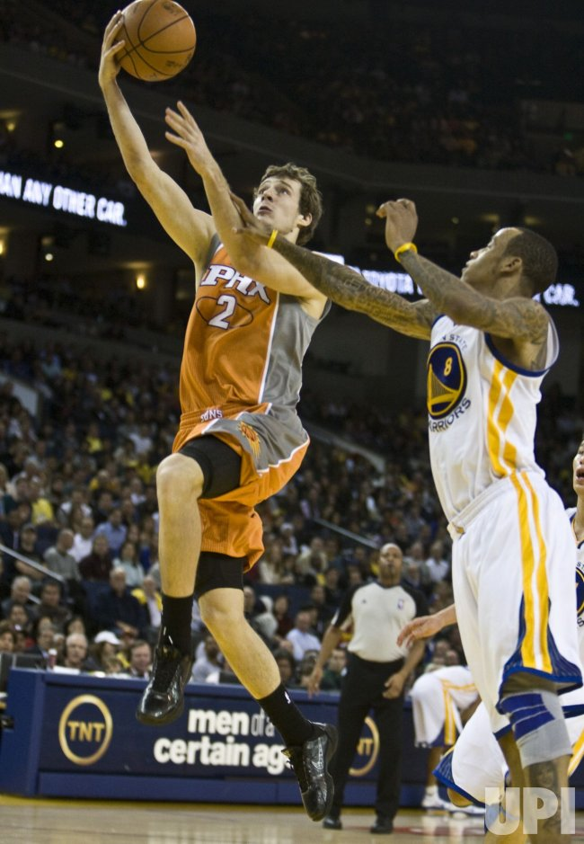 Phoenix Suns Goran Dragiic drives to the hoop past Golden State Warriors Monta Ellis in in Oakland, California