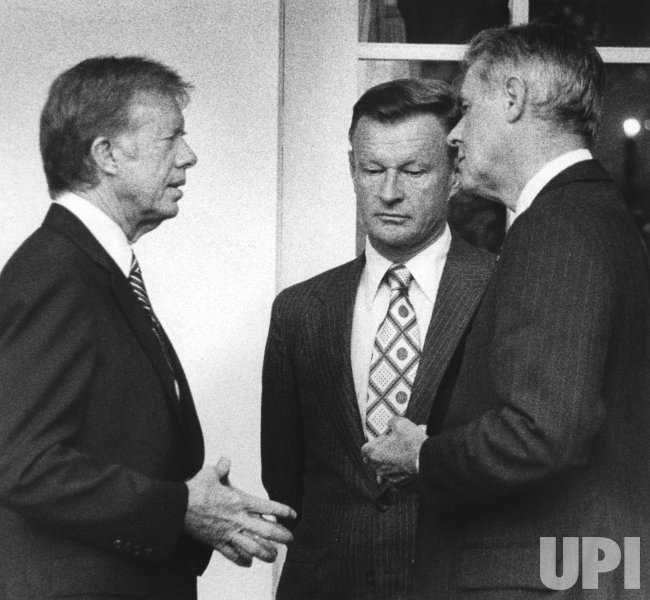President Carter talks with Zbigniew Brzezinski and Cyrus Vance