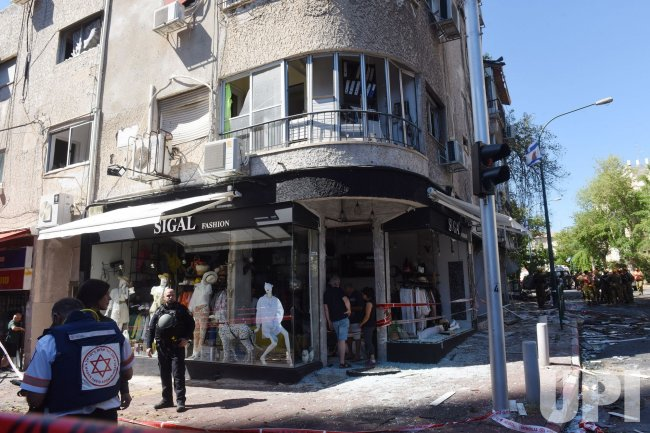 A Police Stands Outside A Fashion Store Damaged From A Rocket