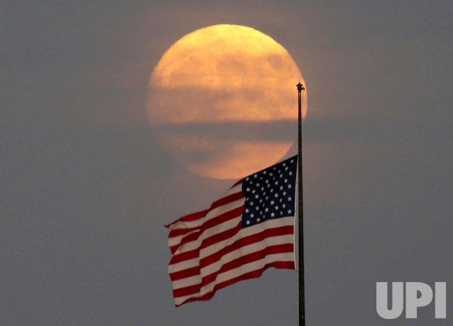 Full Moon Rises Behind an American Flag