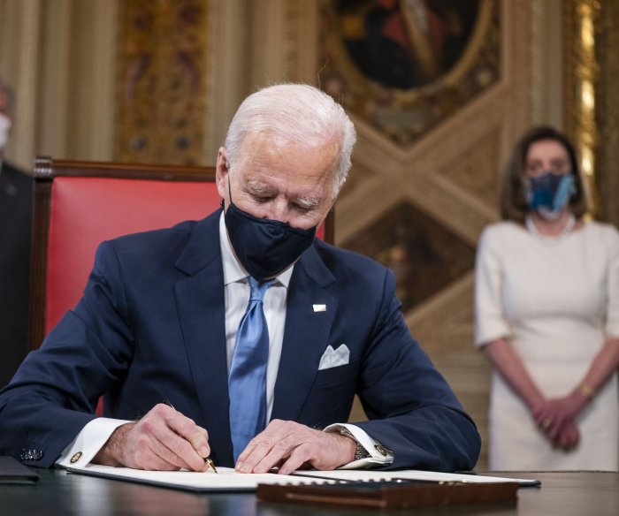 Biden signs executive orders on COVID-19, climate change, DACA