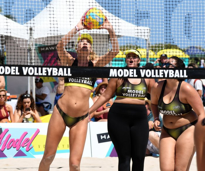 Models take part in a beach volleyball tournament in Miami Beach