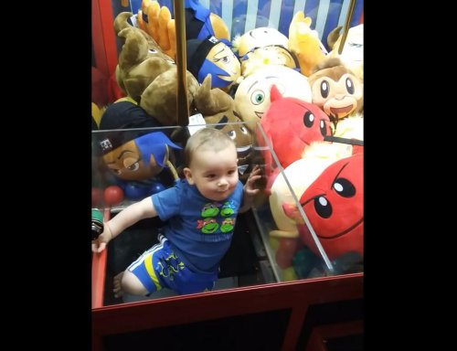 Wandering-toddler-climbs-into-claw-machine