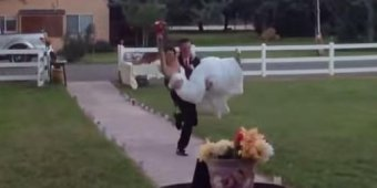 Groom carries bride, falls on top of her [VIDEO]