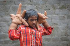 Indian boy with hands larger than his head can't even tie shoes
