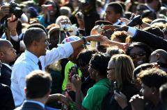 Obama campaigning, fighting attack ads