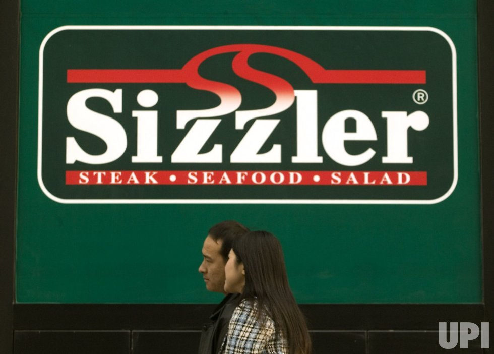 Chinese pedestrians walk past a Sizzler