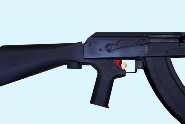 A bump stock permits the trigger (red) to be held down when the receiver moves forward, being reset each round by receiver recoil, allowing semi-automatic firearms to somewhat mimic fully automatic weapons. Photo by Phoenix7777/Wikimedia Commons