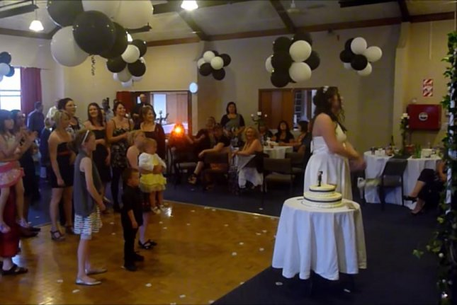A New Zealand bride prepares to throw her bouquet while a young guest prepares to drop her baby sister. LivTheGinjaNinja/YouTube video screenshot