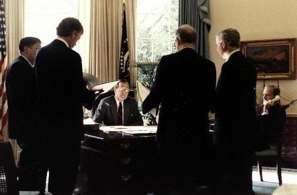 President George H.W. Bush talks with his staff (Gov. Sununu, VP Quayle, Sec. Cheney, Robert Gates, and Sec. Baker) before announcing a 24-hour deadline for Iraq to withdraw from Kuwait in response to the Soviet Peace Proposal to Iraq on November 29, 1991. Photo courtesy of George H.W. Bush/Facebook