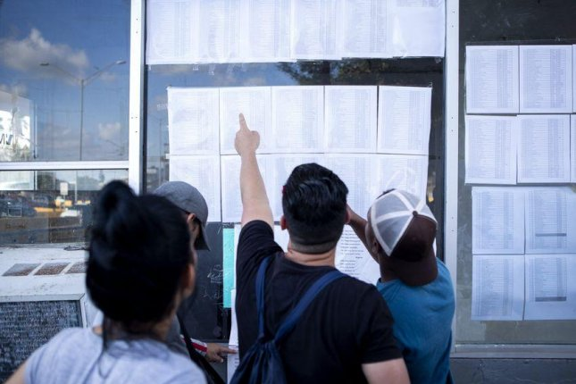 A group of Cuban migrants look at a list of asylum seekers near the Gateway International Bridge in Matamoros, Tamaulipas, Mexico. Photo by Miguel Gutierrez Jr./The Texas Tribune