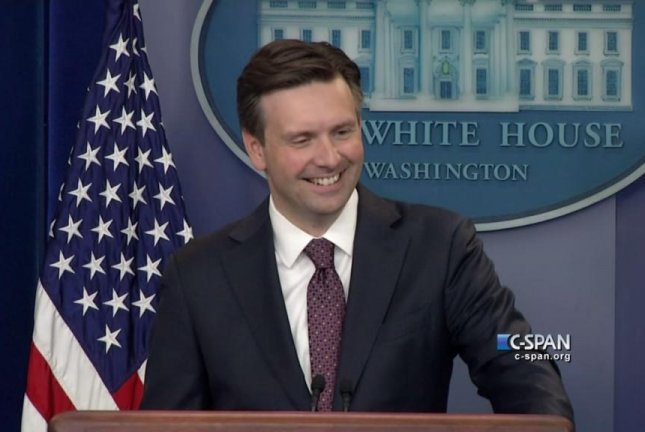 White House Press Secretary Josh Earnest laughs after Siri interrupts a reporter's question about the Iran nuclear deal. C-SPAN/YouTube video screenshot