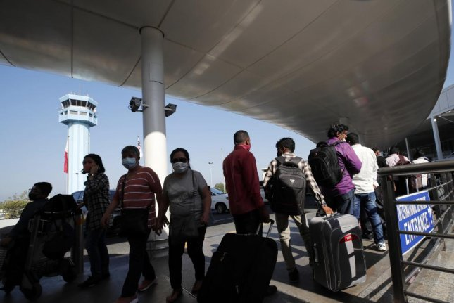 Departing passengers wearing protective masks queue up to enter Ninoy Aquino International Airport in Manila, Philippines, on Wednesday. Photo by Francis R. Malasig/EPA-EFE
