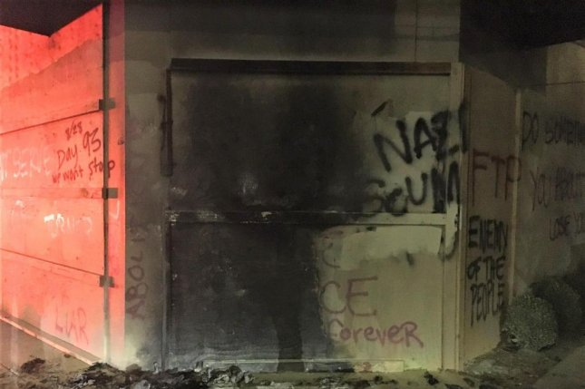 Demonstrators set an object on fire near the boarded-up Portland Police Association building early Saturday, following a demonstration earlier in the evening in the lobby of Mayor Ted Wheeler's condominium building. Photo courtesy Portland Police Bureau