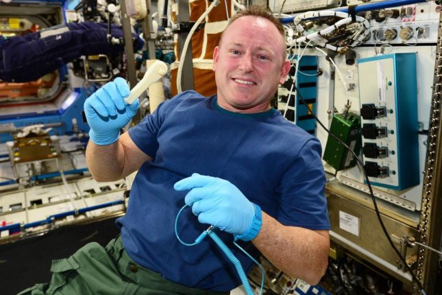 International Space Station Commander Barry Wilmore shows off his brand new ratcheting socket wrench, printed aboard the station. Photo by NASA/Made In Space