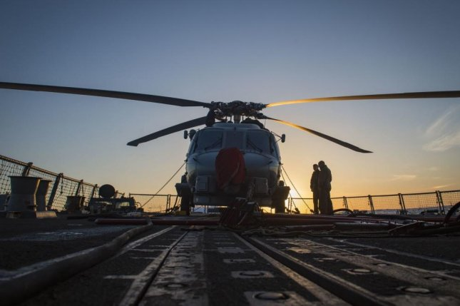 An MH-60R Seahawk assigned to the 'Proud Warriors' of Helicopter Maritime Strike Squadron 72 sits on the flight deck of the guided-missile destroyer USS Farragut as Sailors prepare to transfer it to inside the ship's hangar bay. Photo by Mass Communication Specialist 3rd Class Cameron M. Stoner/U.S. Navy