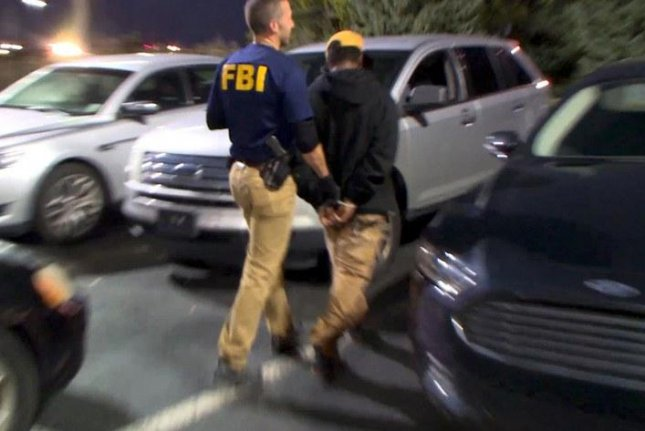 An FBI agent arrests a suspected pimp in Detroit as part of Operation Cross Country, an annual action by the agency to rescue children from sex trafficking and catch the adults abusing and pimping them. Photo courtesy Federal Bureau of Investigation