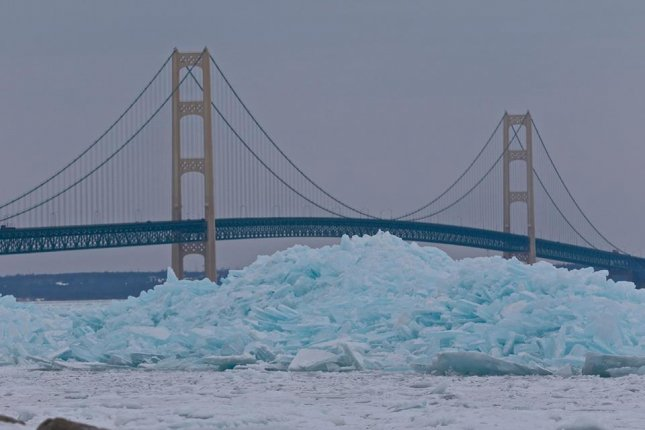 Large heaps of blue snow piled up near Michigan's Mackinac Bridge. The phenomenon is occurs when the molecules in the snow become so dense that they absorb less red light and begin to reflect the blue color.  Photo by Kelly Shupe Alvesteffer/Facebook