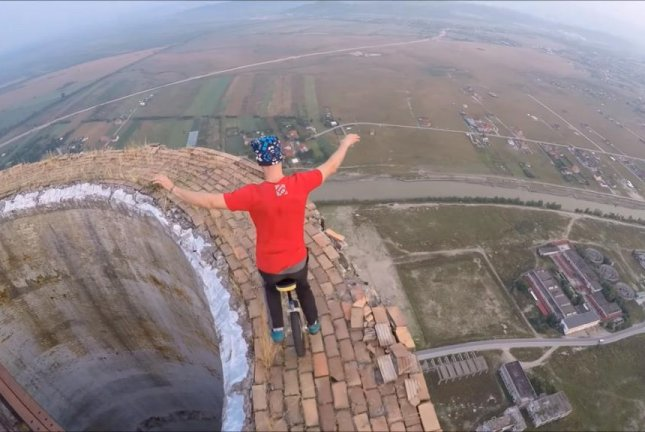 Flaviu Cernescu rides his unicycle high over a Romanian town. Screenshot: Storyful
