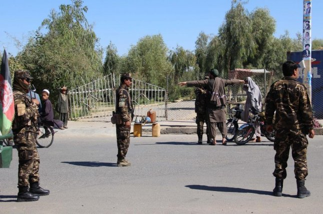 Afghan security officials check people and vehicles on a road side as security has been intensified ahead of parliamentary elections in Helmand, Afghanistan, on October 19. On Friday, 26 Afghan troops were killed in a bomb attack on a mosque. Photo by Watan Yar/EPA-EFE