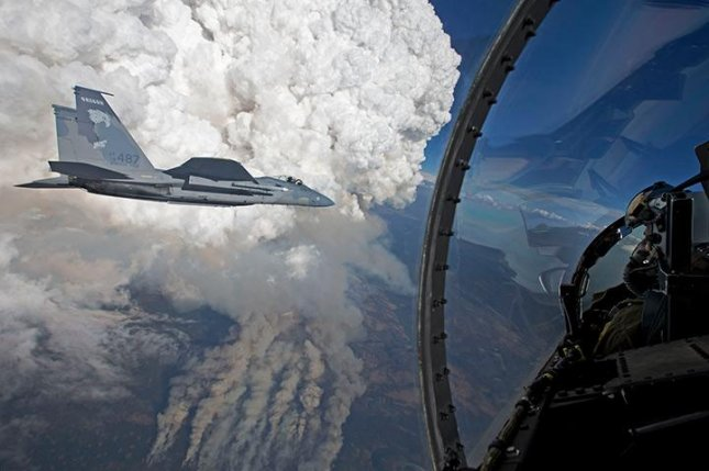 Fighter jets with the Oregon Air National Guard fly by fire clouds. (Photo by James Haseltine and the Oregon Air National Guard 173rd Fighter Wing)