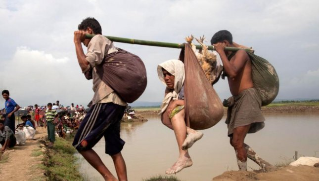 Rohingya Muslims assist an elderly woman as they escape Myanmar to Teknaf, Bangladesh, on Monday. Over 123,000 ethnic Rohingya have fled violence in Myanmar in the past two weeks, the United Nations said. Photo by EPA-EFE/STR