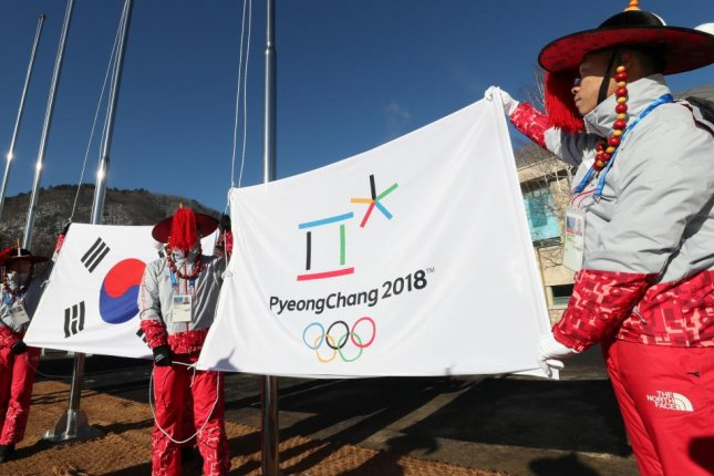 Organizers of the Pyeongchang Olympics practice raising the national flag of South Korea and the Olympic flag at the athletes' village in Pyeongchang, Gangwon Province, on Feb. 1. Photo by Yonhap