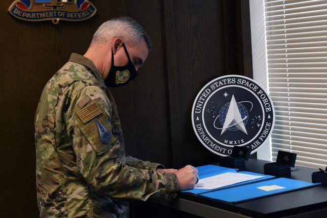 Maj. Gen. Stephen Whiting, Headquarters United States Space Force deputy commander, signs three USSF recruits contracts at the Denver Military Entrance Processing Station Oct. 20, 2020. Photo by Haley N. Blevins/U.S. Space Force